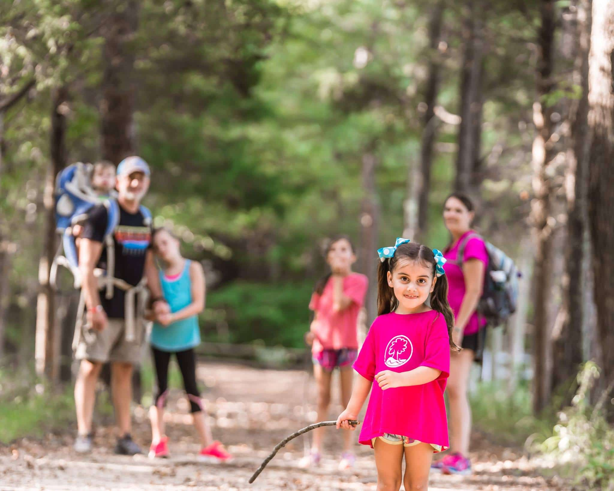 Family hiking in the woods with little girl smiling