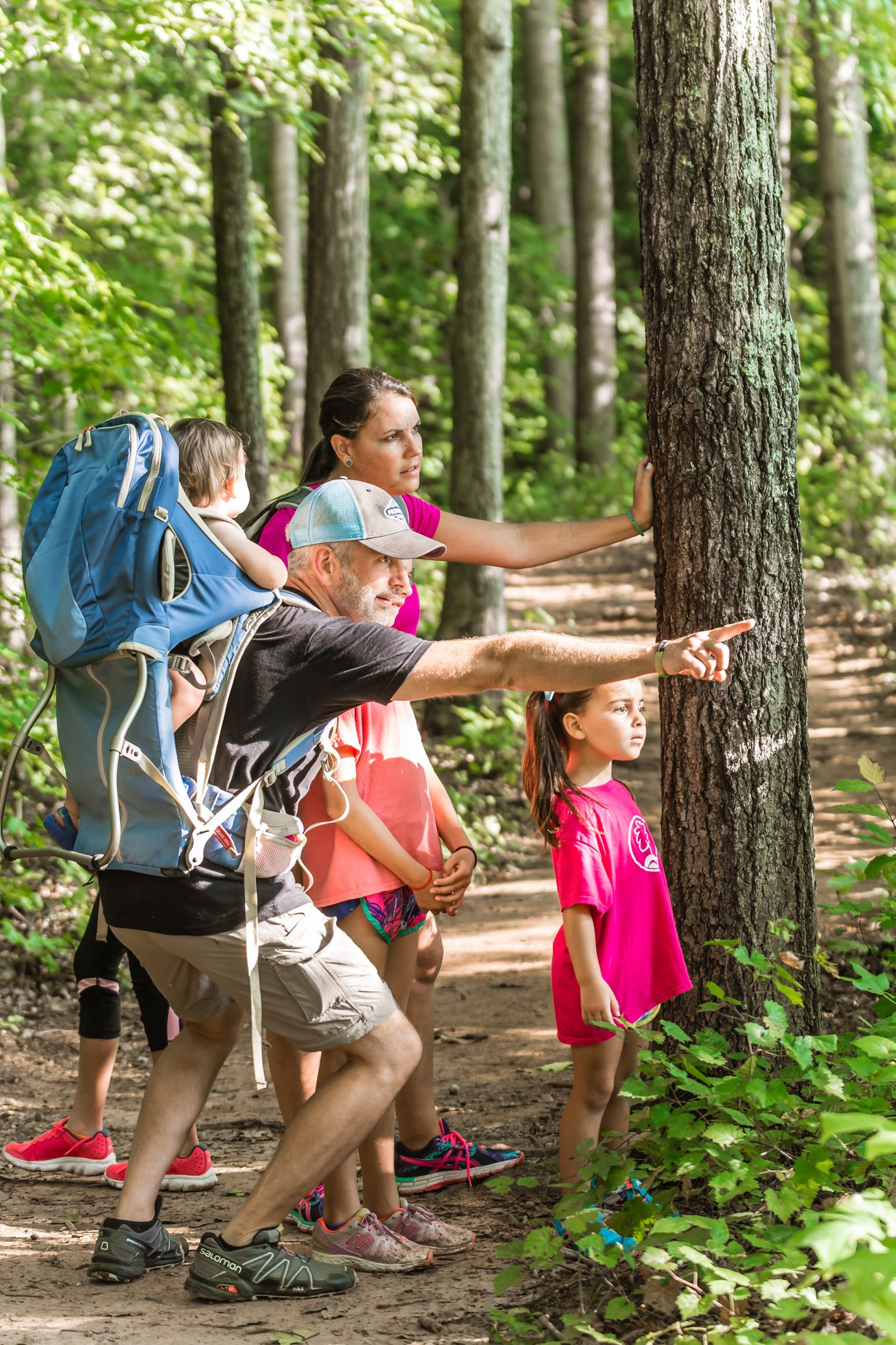 Family pointing at something in the woods