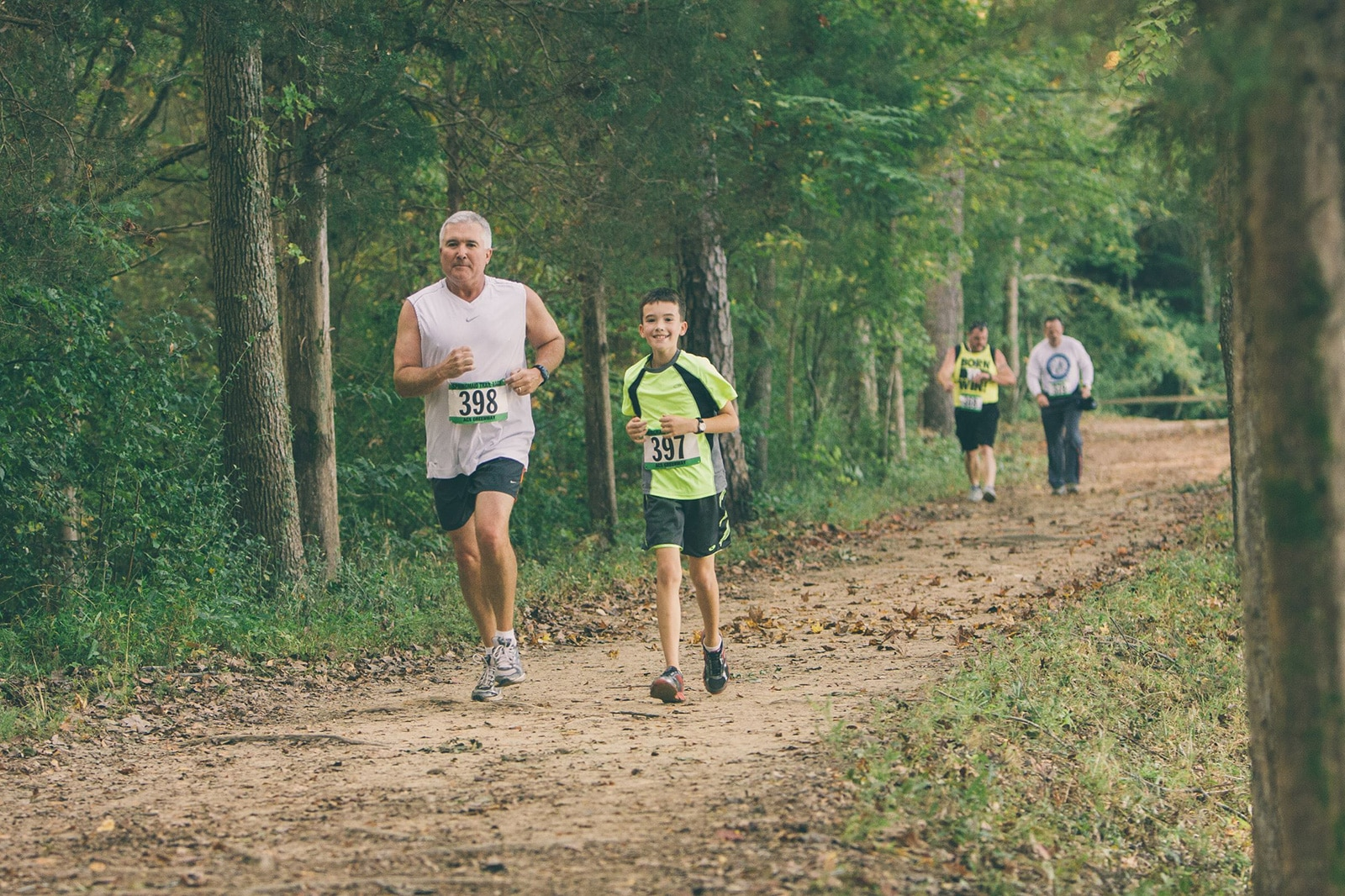 Father and son running a race in the woods