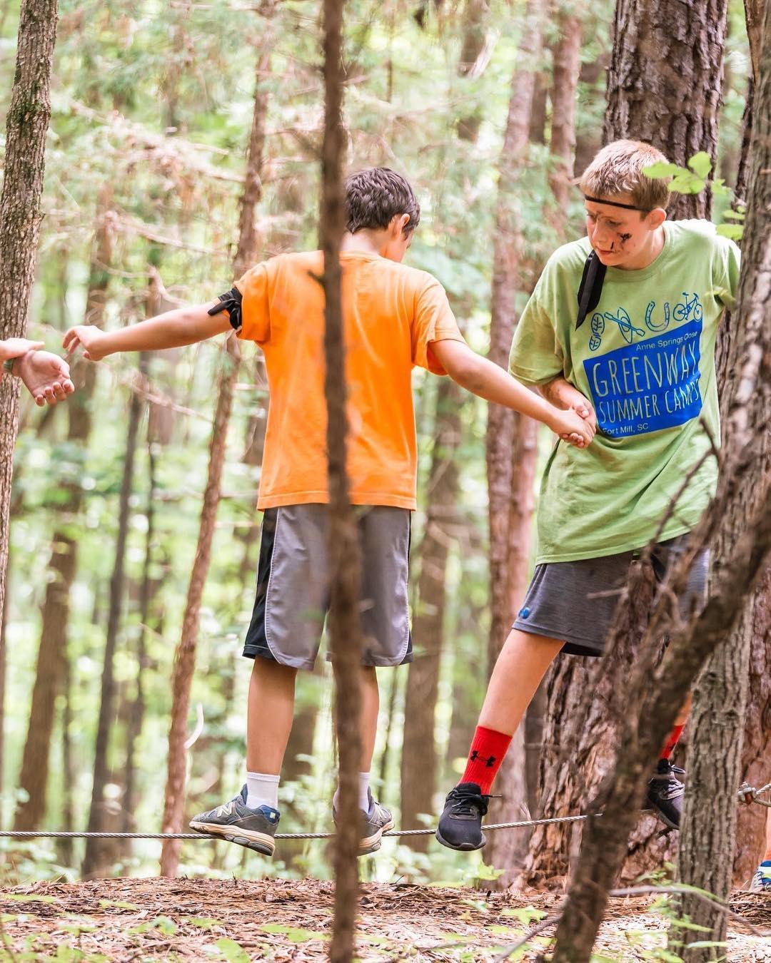 Boys walking slack line at Greenway Summer Camp