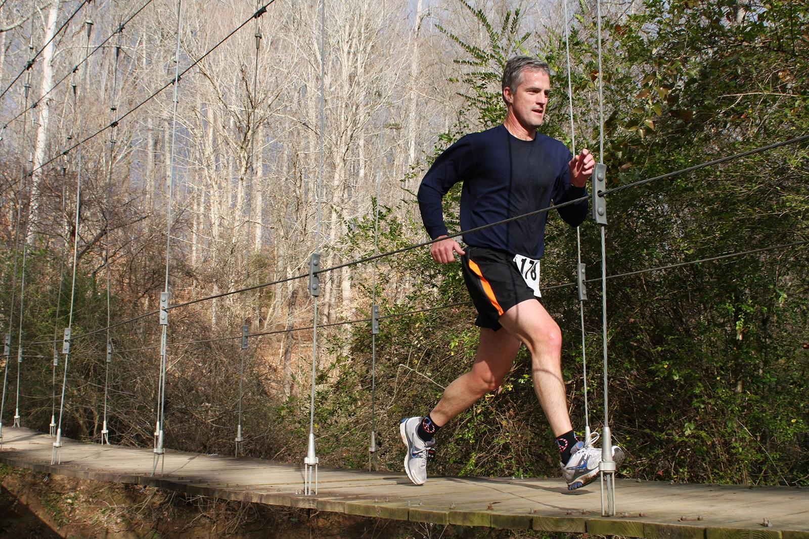 Man running across suspension bridge in race
