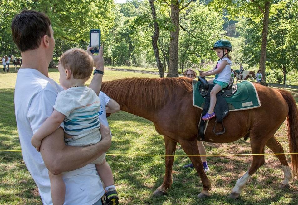 Man taking photo of girl on horse