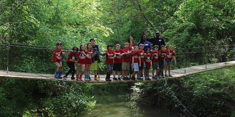 Group of school kids on a field trip standing on a bridge