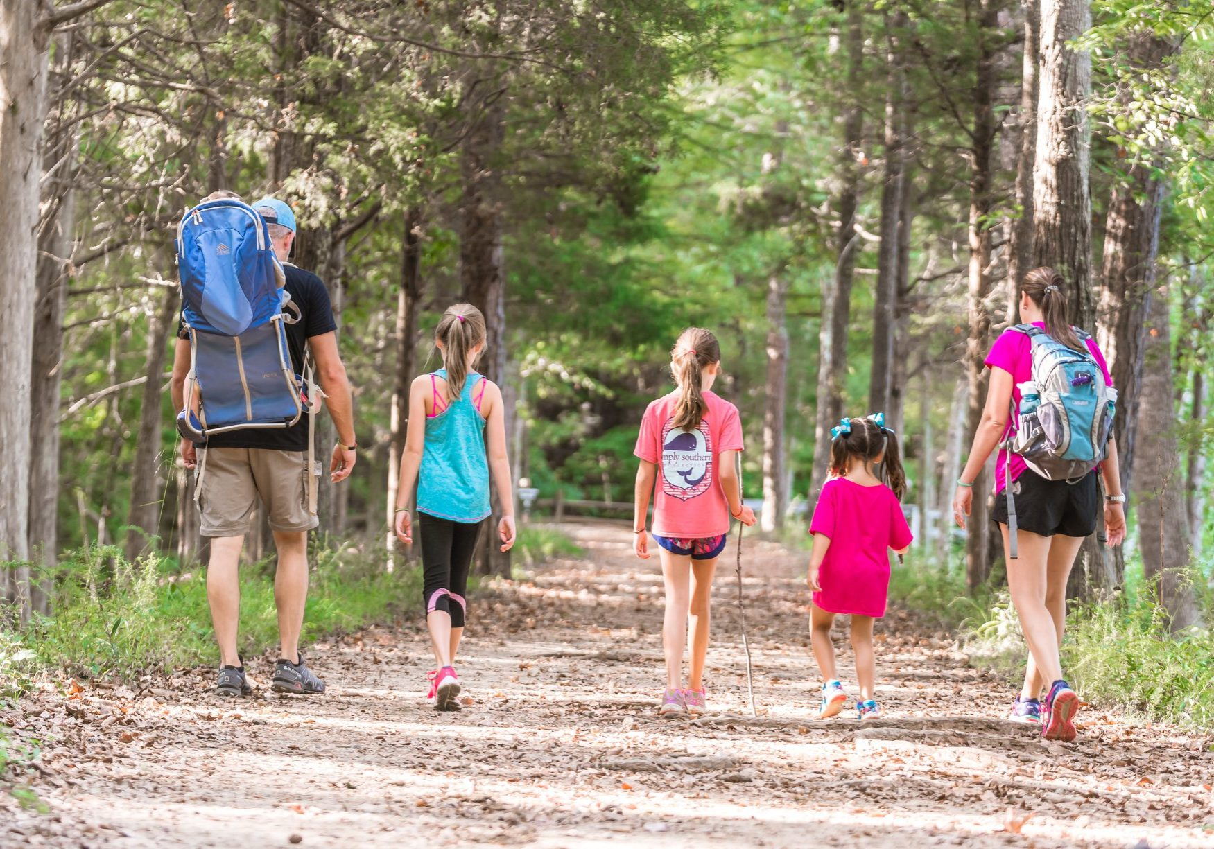 Family hiking down a path in the Greenway